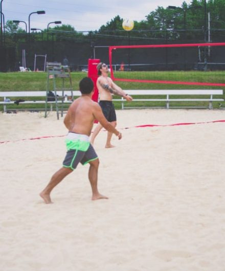 men playing beach volleyball at fitness center