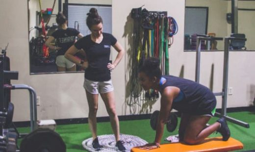 personal trainer coaching woman through exercise