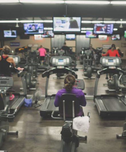 gym members using cardio equipment while watching tv