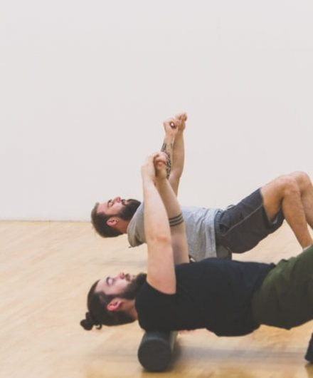 men using foam rollers in spacious studio