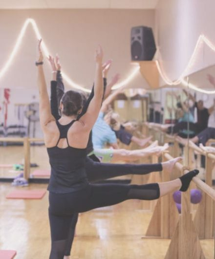gym members participating in barre class inside spacious fitness studio
