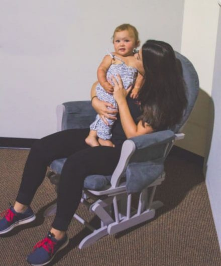 mother holding baby at gym daycare