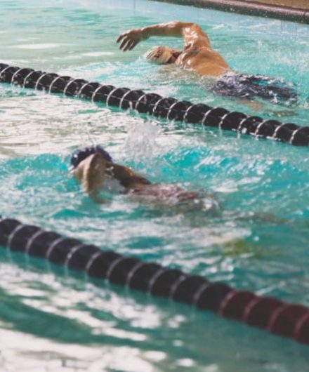 swimmers racing in indoor pool