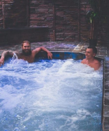 men relaxing in large jacuzzi at best gym near me