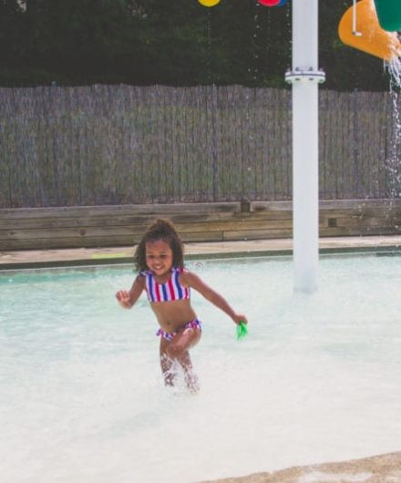 little girl playing in splash park at gym