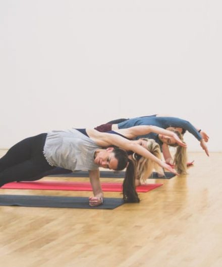 women on mats doing pilates in spacious studio