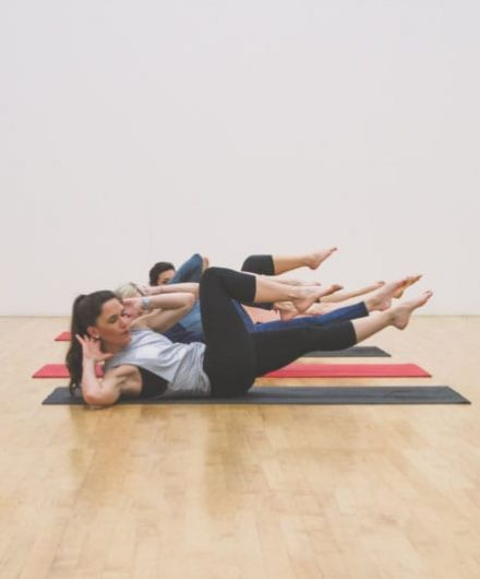 women on mats doing pilates in class
