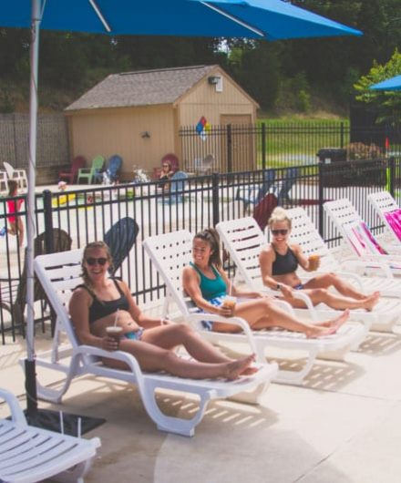 women sitting around large outdoor pool at sportscenter