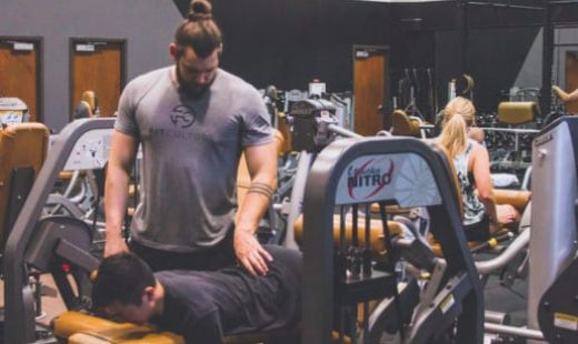 personal trainer correcting lifting technique of trainee