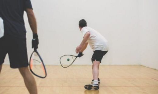 man hitting ball in racquetball game