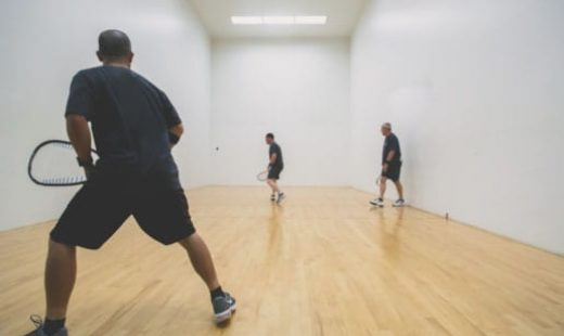 man hitting ball in spacious racquetball court