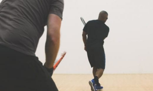 man hitting ball in racquetball