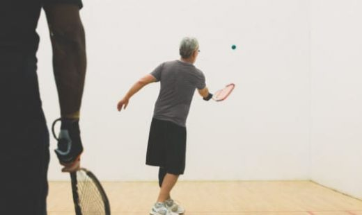 man hitting ball against wall in racquetball