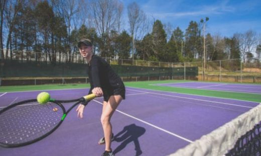 woman hitting ball on tennis court
